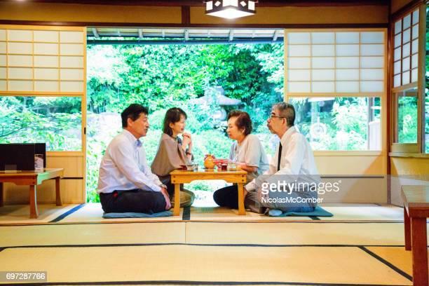 Four elderly Japanese friends enjoy social meeting in garden restaurant