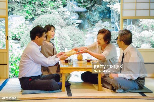 vier oudere japanse vrienden wisselen geschenken bij sociale bijeenkomst - social grace stockfoto's en -beelden