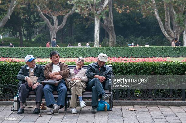 Four elderly men relax on a park bench in Fuxing Park, Luwan District , Shanghai. Two sleep, one takes his shoes off, one watches the passersby but...
