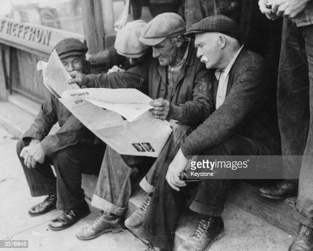 Four elderly men sitting on a step reading a newspaper during the Great Depression.