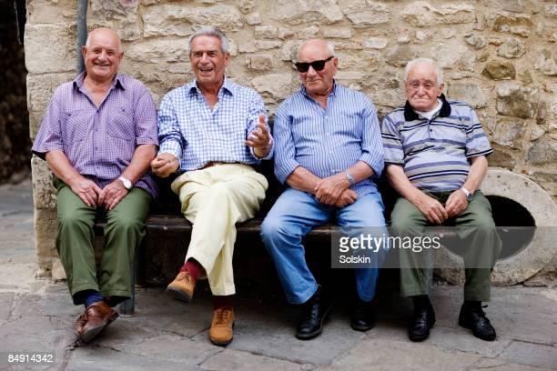 Four elderly men sitting on an outside bench