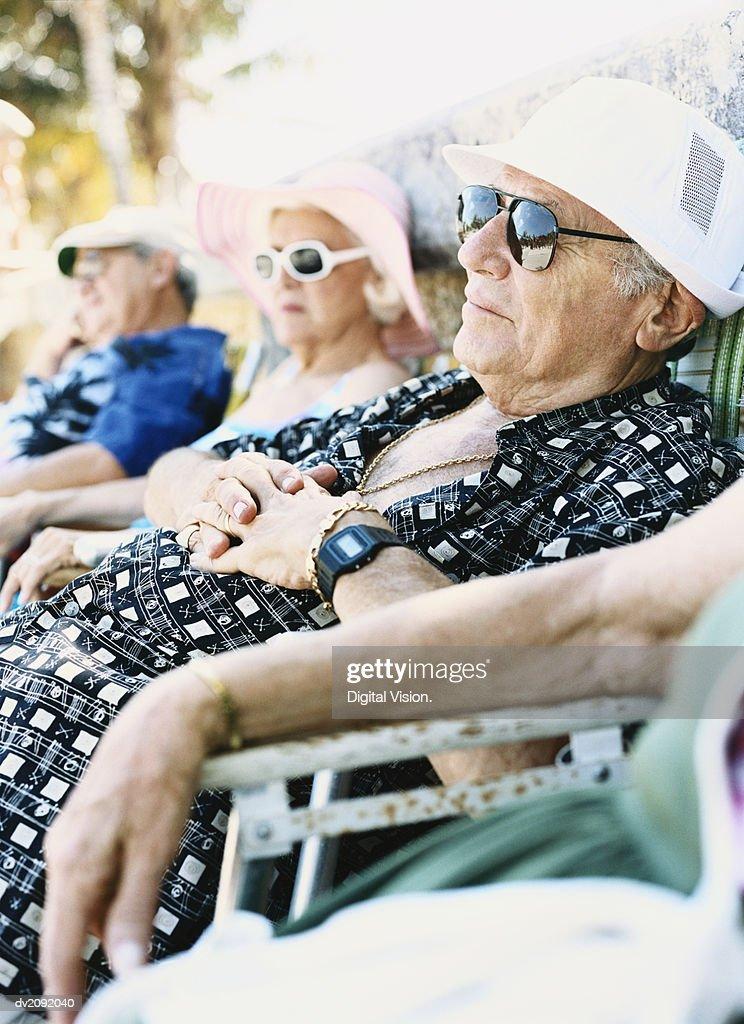 Four Elderly People Sit on Chairs Sunbathing : Stock Photo