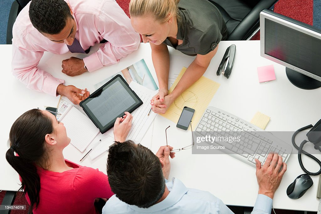 Four employees gathered around a digital tablet : Stock Photo