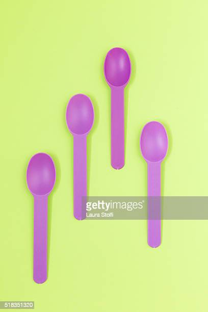 Four empty purple dessert spoons on green background