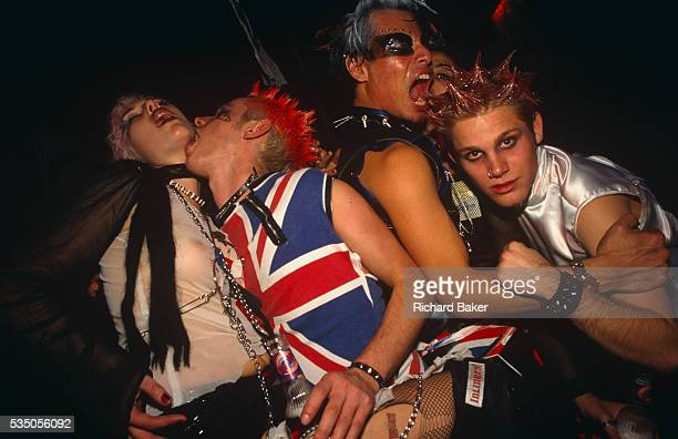 Four energetic party goers are dressed up as eccentric 70s punks at a Halloween event in Adrenaline Village Battersea London UK Taken from below them...