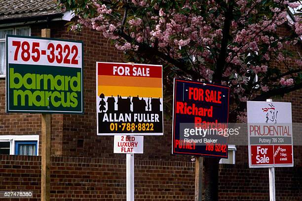 Four estate agent's property boards advertise their names and numbers in a London housing estate each representing vendors selling their houses and...