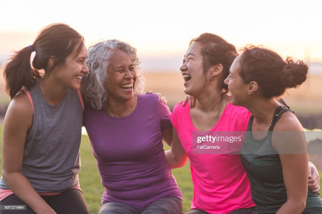 Four ethnic women laughing together after an outdoor workout : Stock Photo