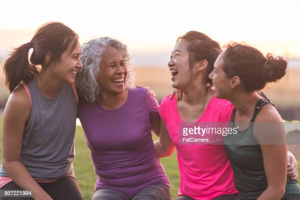 four ethnic women laughing together after an outdoor workout - healthy lifestyle stock pictures, royalty-free photos & images