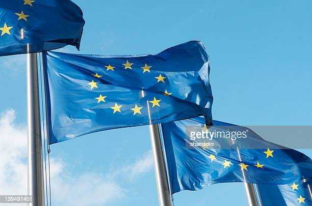 four european union flags waving in the wind - flag stock pictures, royalty-free photos & images