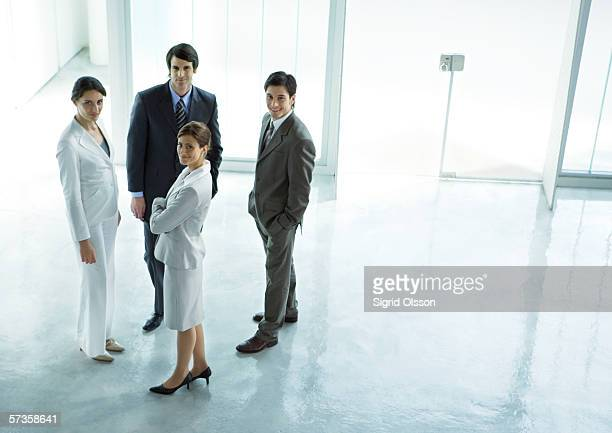 Four executives standing in office building lobby