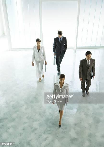 Four executives walking through office building lobby