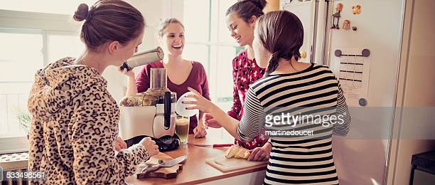 Four expressive roommates using a juicer in their appartement kitchen.