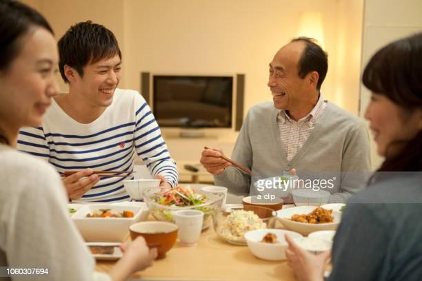 夕食をとる家族4人 - ダイニングテーブル ストックフォトと画像