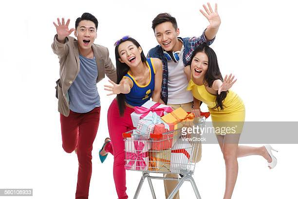 Four fashionable young man pushing a shopping cart