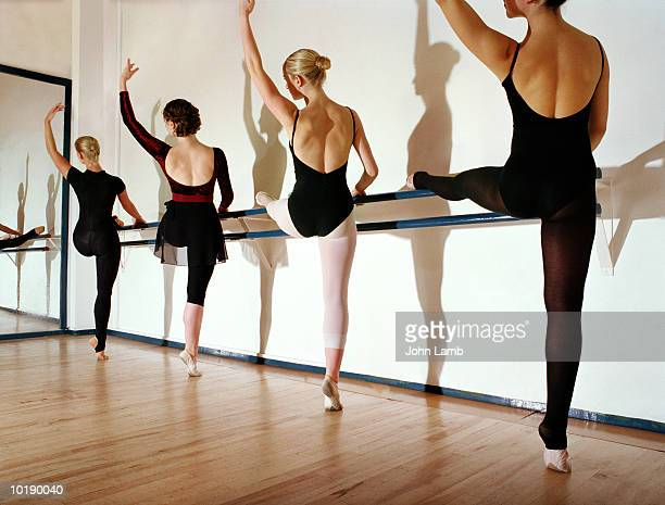 Four female ballet dancers practising at bar, rear view