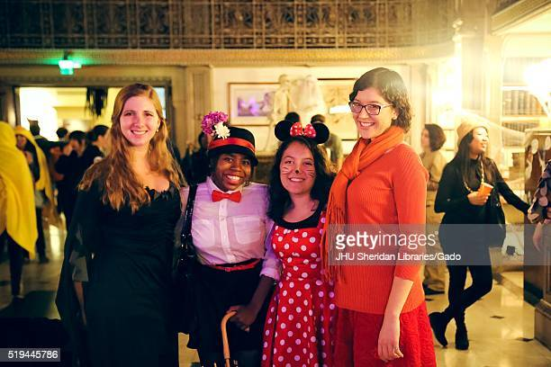 Four female college students are posing and smiling, the girl on the far left is wearing a black dress, the next girl is dressed as Mary Poppins and...