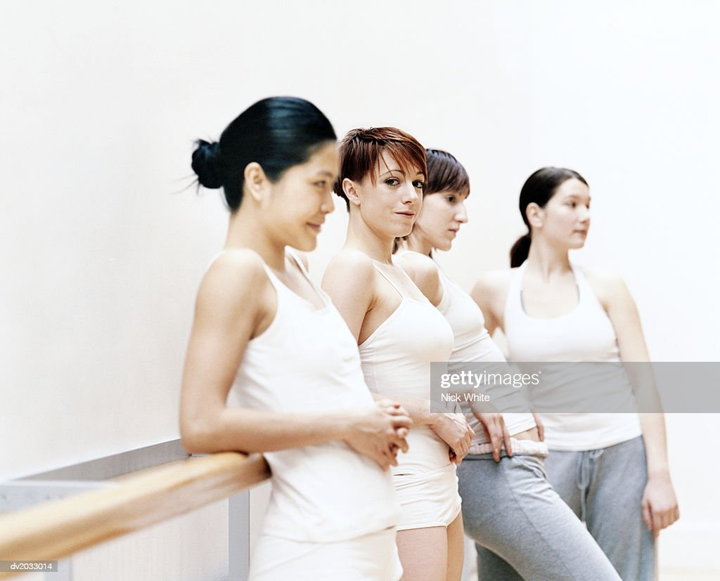 Four Female Dancers Leaning Against a Wall : Stock Photo