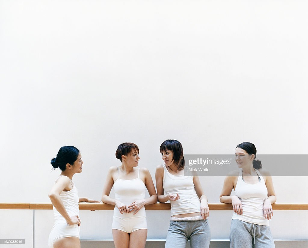 Four Female Dancers Standing in a Line and Talking : Stock Photo