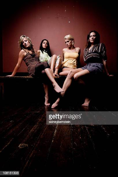 Cuatro mujeres de moda modelos posando en pared