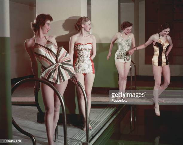 Four female fashion models wearing bathing suits and swimwear in different styles all designed by Klein of Montreal posing by a swimming pool May 1951