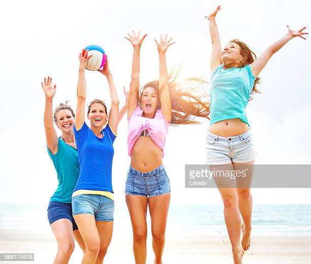 Four female friends playing beach volleyball in the summer