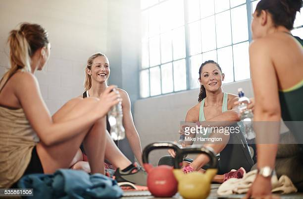 four females in warehouse gym taking a break. - sportswear stock pictures, royalty-free photos & images