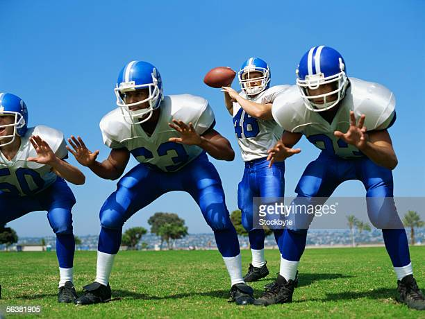 four football players playing on a football field - american football team stock pictures, royalty-free photos & images