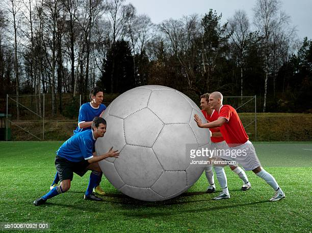 four football players with oversized ball - man with big balls stock photos and pictures