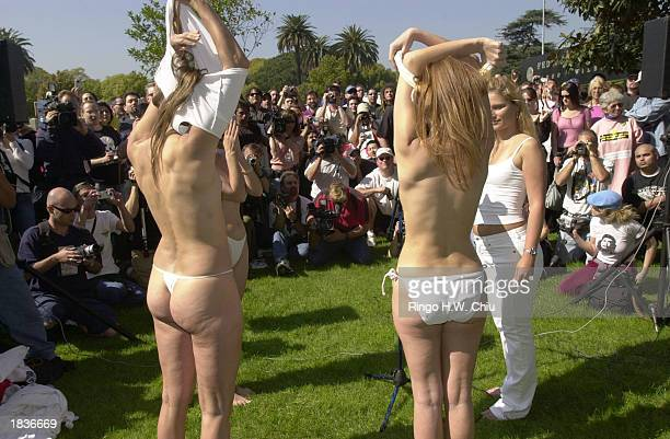 Four French protesters are surrounded by the press while they undress during a women's antiwar march and rally at the Westwood Federal Building March...
