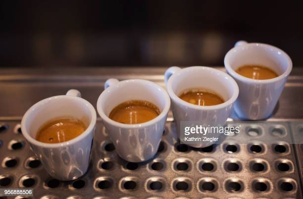 four fresh espressos on bar counter ready to be served - caffeine stock pictures, royalty-free photos & images