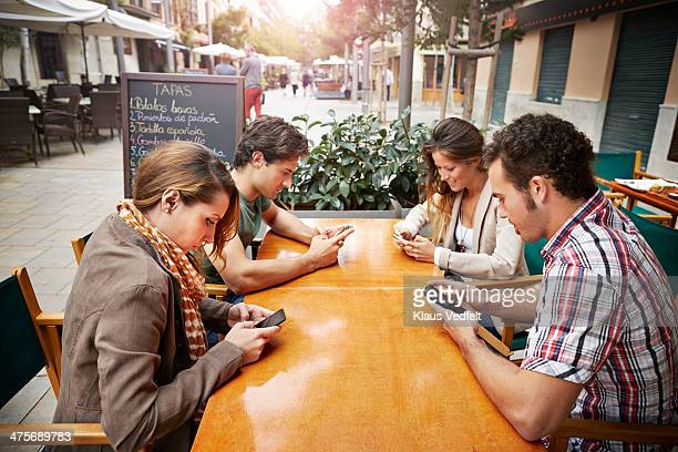 four friends all looking at their phones at cafe - ignoring stock pictures, royalty-free photos & images