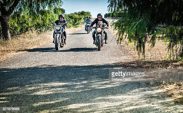 Four friends and one dog riding motorcycles on rural road, Cagliari, Sardinia, Italy