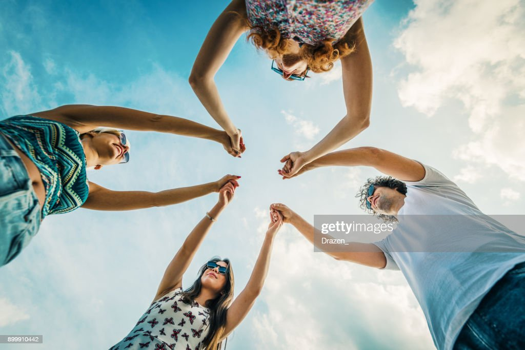 Four Friends At The Beach Holding Their Hands As Sing Of Unity And