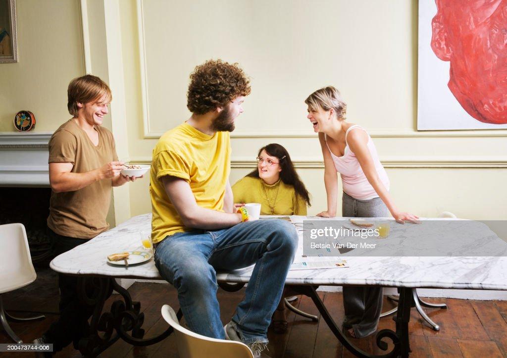 Four friends by table : Bildbanksbilder