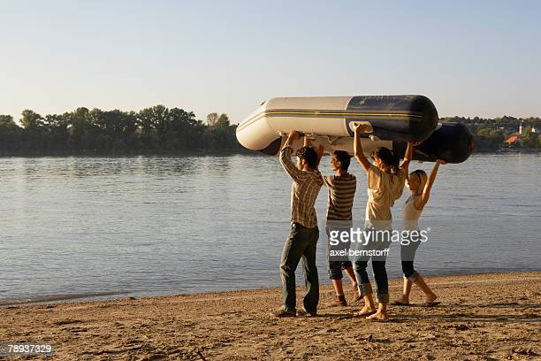 Four friends carrying a raft on a beach.