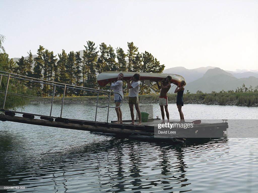 Four Friends Carrying Canoe On Jetty Side View Stock Photo