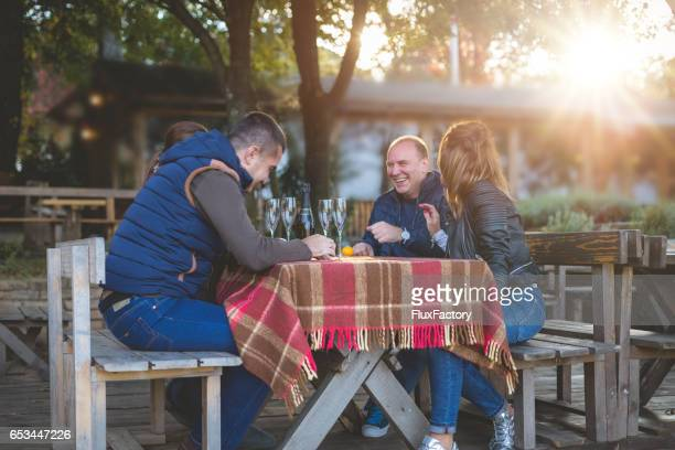 Four friends celebrating outdoors, talking and smiling