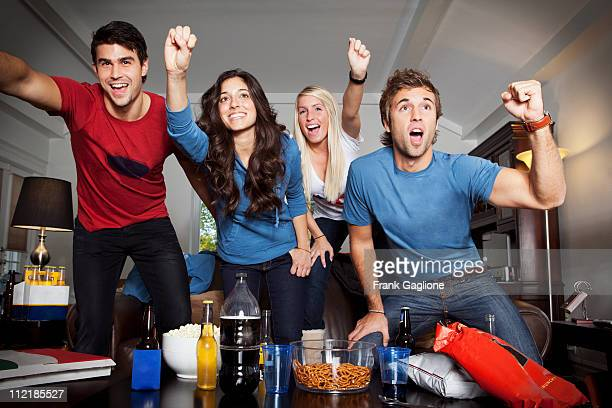 Four Friends Cheering in Front of TV.