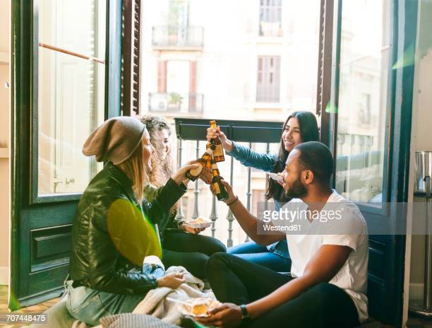 Four friends clinking beer bottles