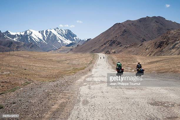 Four friends cycling across the Pamirs mountains of Tajikistan (Central Asia) during a world tour by bicycle