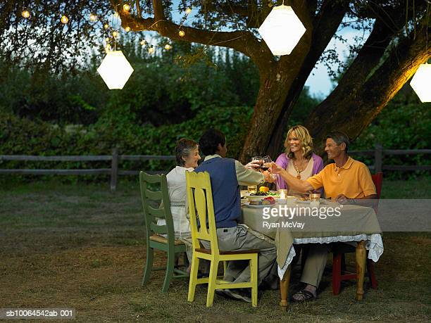 Four friends dining in yard at dusk