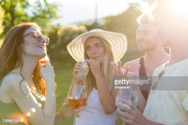 Four friends drinking and talking in the garden
