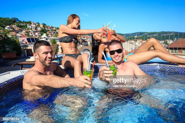 Four friends drinking cocktails on rooftop swimming pool