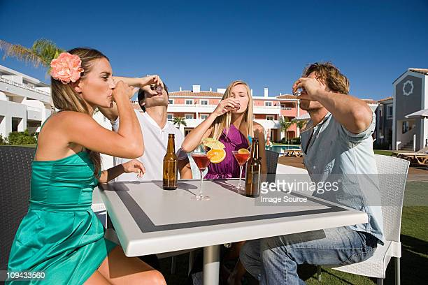 Four friends drinking shots on holiday