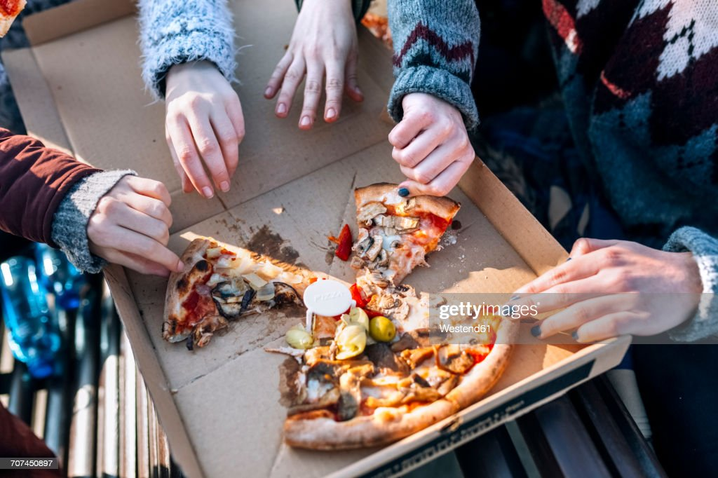 Four friends eating pizza outdoors, partial view : Stock Photo