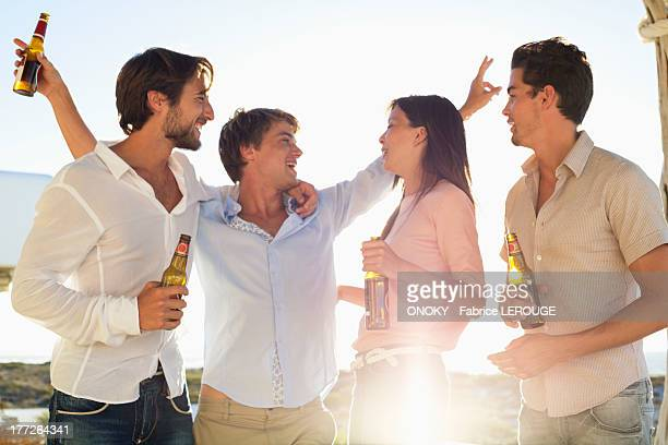 four friends enjoying beer in party - onoky stock-fotos und bilder