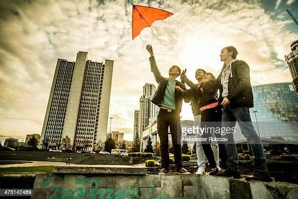 four friends flying kite, russia - nur erwachsene stock-fotos und bilder