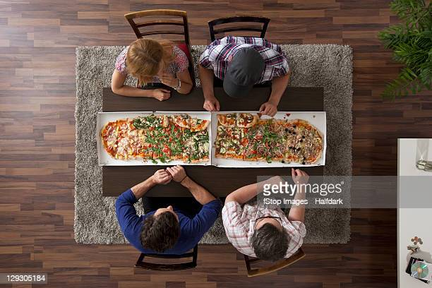 Four friends getting ready to eat two large pizzas, overhead view