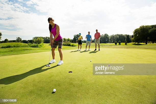 four friends golfing together. - putting stock pictures, royalty-free photos & images