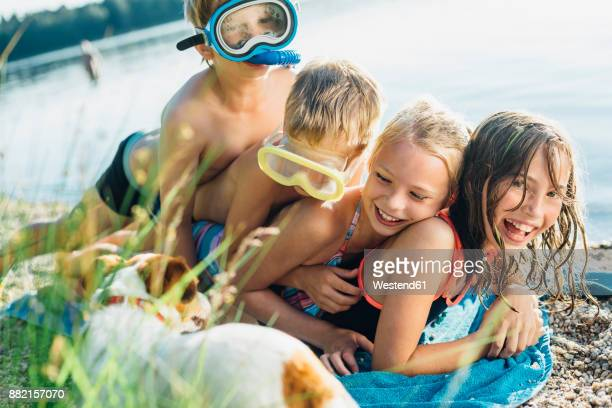 four friends having fun together on the beach - little girl laying on the beach stock photos and pictures
